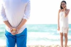 Romantisch concept met de mens die witte ring houden die aanzoek in het strand maken De Aziatische wittebroodsweken van de paarmi royalty-vrije stock afbeelding