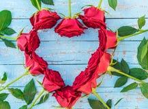 Romantisch die liefdehart van rode rozen op lichtblauw hout voor Huwelijk, Valentijnskaarten of Moedersdag wordt gemaakt Stock Foto's