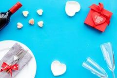 Romantisch diner op de Dag van Valentine Verfraaide schotels, vaatwerk, wijn en giftvakje op blauw achtergrond hoogste meningsexe stock fotografie