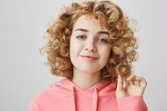Romantisch en leuk jong Kaukasisch meisje met krullend haar wat betreft krul met hand en het glimlachen bij camera, die in goede  stock afbeeldingen