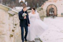 Romantisch enloved jonggehuwdepaar die dichtbij oude kasteelmuur lopen na huwelijksceremonie Stock Foto