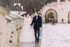 Romantisch enloved jonggehuwdepaar die samen dichtbij oude kasteelmuur wandelen Stock Afbeeldingen