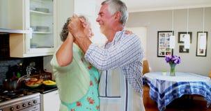 Romantisch hoger paar die in keuken 4k dansen stock videobeelden