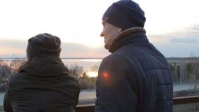Romantisch jong paar die genietend van zonsondergang op cityscape van het dakbalkon ontspannen stock videobeelden