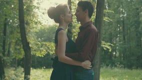 Romantisch jong paar die in park koesteren Portret van zonsondergang het gelukkige mensen stock videobeelden