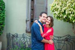 Romantisch jong paar in heldere rode en blauwe kleren die en het lachen het kijken aan camera op de mediterrane stijlstraat omhel Stock Afbeeldingen