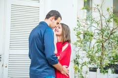 Romantisch jong paar in heldere rode en blauwe kleren die op de witte blokhuisachtergrond omhelzen Liefde, Romaans dateren, Lifes Stock Afbeelding
