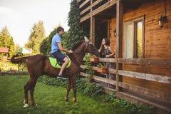 Romantisch jong paar in liefde, een gang op een paard op aardachtergrond en houten land-stijl hotel Een mens zit schrijlings op Royalty-vrije Stock Foto
