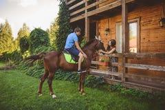 Romantisch jong paar in liefde, een gang op een paard op aardachtergrond en houten land-stijl hotel Een mens zit schrijlings op Royalty-vrije Stock Fotografie