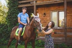 Romantisch jong paar in liefde, een gang op een paard op aardachtergrond en houten land-stijl hotel Een mens zit schrijlings op Stock Fotografie