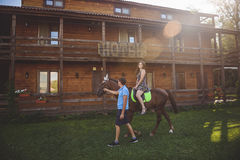 Romantisch jong paar in liefde, een gang op een paard op aardachtergrond en houten land-stijl hotel Jonge Vrouw 15 Stock Foto