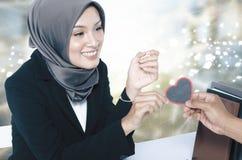 Romantisch kijk het hartsymbool van de handholding van hout over vage achtergrond wordt gemaakt die Royalty-vrije Stock Foto's