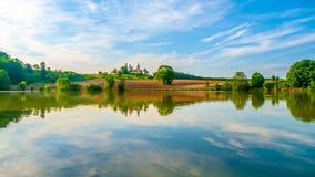 Romantisch landschap met kleine die kerk op de heuvel in de vijver wordt weerspiegeld Zonnige de zomerdag met blauwe hemel en wit Stock Afbeeldingen
