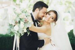 Romantisch, Märchen, glückliche Jungvermähltenpaare, die in einem Park, Bäume im Hintergrund umarmen und küssen stockbild