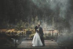 Romantisch, Märchen, glückliche Jungvermähltenpaare, die in einem Park, Bäume im Hintergrund umarmen und küssen stockfoto
