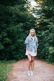 Romantisch meisje in openlucht Lang haar Meisje in een blauwe kleding met een hoofdpijn op een gebied bij zonsondergang in de zom stock foto's