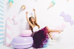 Romantisch meisje in in witte gehielde schoenen die pret op haar verjaardagspartij hebben, die op stuk speelgoed koekje zitten di stock foto