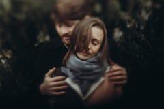 Romantisch modieus paar die zacht in de herfstpark koesteren mens en w Stock Afbeeldingen