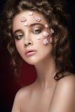 Romantisch naakt jong mooi meisje met witte bloemen op haar gezicht en zachte krullen op donkere achtergrond Stock Afbeelding