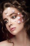Romantisch naakt jong mooi meisje met witte bloemen op haar gezicht en zachte krullen op donkere achtergrond Stock Foto's