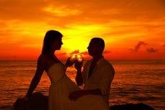 Romantisch paar bij tropisch strand met zonsondergang op de achtergrond Stock Afbeeldingen