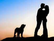 Romantisch paar bij zonsondergang met hun hond royalty-vrije stock afbeelding