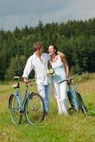 Romantisch paar dat met oude fiets in weide loopt Royalty-vrije Stock Fotografie