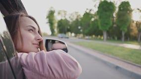 Romantisch paar in de auto Een jong mooi meisje geniet van het de zomerlandschap door het open venster van een bewegende auto stock video