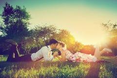Romantisch paar die in liefde terwijl het liggen op gras kussen wijnoogst
