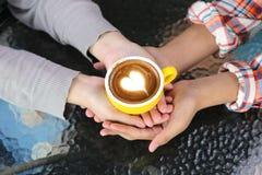 Romantisch paar die in liefdehand twee koppen van lattekunst houden met patroon het hart op lijst in koffiewinkel stock foto