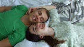 Romantisch paar die op het bed face to face liggen stock videobeelden