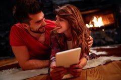 Romantisch paar die op vloer leggen en tablet thuis gebruiken Royalty-vrije Stock Afbeelding