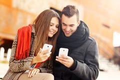 Romantisch paar die slimme telefoons met behulp van tijdens de herfstgang Royalty-vrije Stock Afbeeldingen