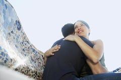 Romantisch Paar die terwijl het Zitten op Steenbank omhelzen Stock Foto's