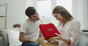 Romantisch paar die thuis, de Dag van Valentine s, het jonge kerel geven vieren huidig voor zijn jonge dame, zeer is zij stock videobeelden