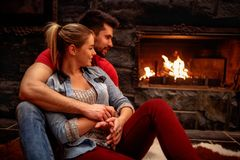 Romantisch paar die thuis voorzijde van open haard koesteren Royalty-vrije Stock Foto