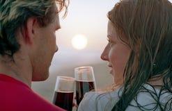 Romantisch paar met drinkbeker wijn op een strand stock foto