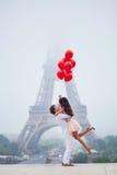 Romantisch paar met rode ballons samen in Parijs stock afbeelding