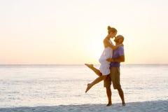 Romantisch paar op het strand bij kleurrijke zonsondergang Royalty-vrije Stock Afbeelding