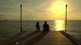 Romantisch paar op het strand bij kleurrijke zonsondergang op achtergrond stock video