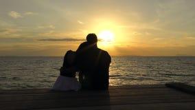 Romantisch paar op het strand bij kleurrijke zonsondergang op achtergrond stock footage