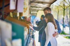 Romantisch paar in Parijs die een boek van een boekhandelaar selecteren stock foto's