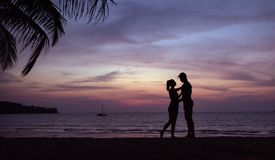 Romantisch portret van een paar die op een tropische brach koesteren - zonsondergangomstandigheid stock afbeeldingen