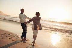 Romantisch rijp paar die van een dag genieten bij het strand stock afbeeldingen