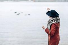 Romantische ältere Frau, die geht, Vögel einzuziehen stockfoto