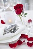 Romantische Abendesseneinstellung mit den rosafarbenen Blumenblättern Lizenzfreies Stockfoto