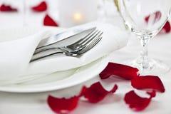 Romantische Abendesseneinstellung mit den rosafarbenen Blumenblättern Stockbild