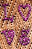 Romantische achtergrond op antieke houten en purpere hierboven geïmponeerde woordliefde stock afbeeldingen