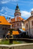 Romantische Ansicht des Schloss-Turms und des Brunnens im Hof in Cesky Krumlov lizenzfreie stockfotos