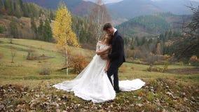 Romantische Atmosphäre der liebevollen Paare der Jungvermählten, die weich in den mounatins im Herbst umarmen Der Bräutigam küsst stock video footage